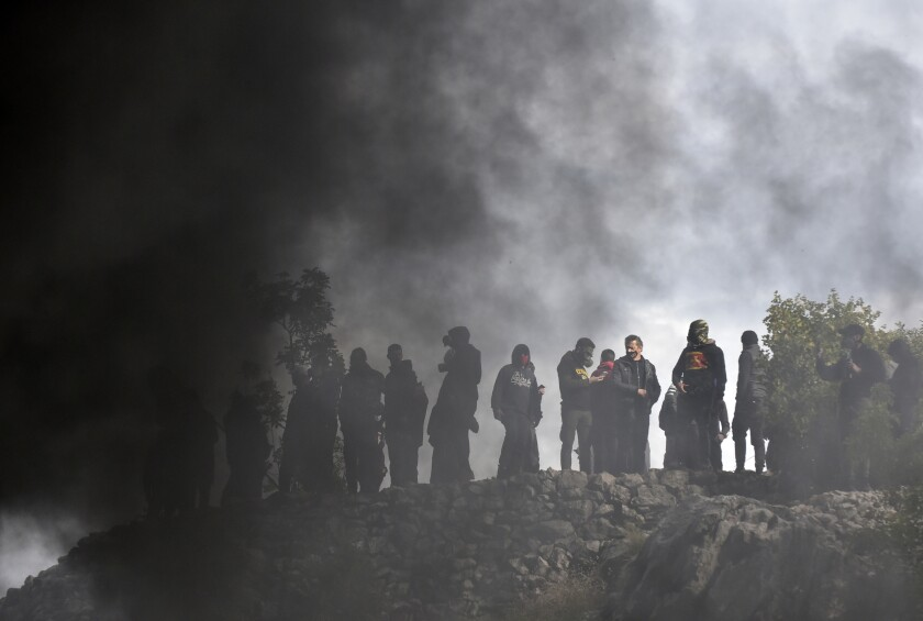 Protesters stand at one of the blockades during a protest against the inauguration of Metropolitan Joanikije, near Cetinje, Montenegro, Sunday, Sept. 5, 2021. Riot police used tear gas on protesters who fired gunshots in the air and hurled bottles and stones early Sunday in Montenegro before a planned inauguration of the new head of the Serbian Orthodox Church in the country. The ceremony scheduled in Cetinje, a former capital of the small Balkan nation, has angered opponents of the Serbian church in Montenegro, which declared independence from neighboring Serbia in 2006. (AP Photo/Risto Bozovic)