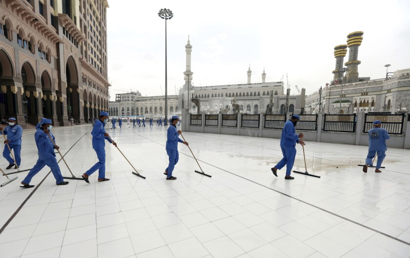 Monday, July 27, 2020, workers disinfect the ground outside the Grand Mosque, over fears of the new coronavirus.