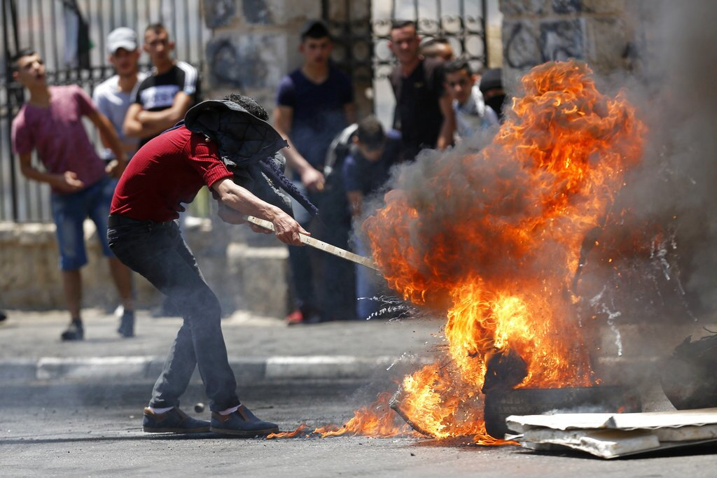 """Palestinians burn tires during clashes with Israeli forces after a rally to mark the 70th anniversary of what Palestinians call their """"nakba,"""" or catastrophe — the uprooting of hundreds of thousands in the Mideast war over Israel's 1948 creation, in the West Bank city of Bethlehem, Tuesday, May 15, 2018."""