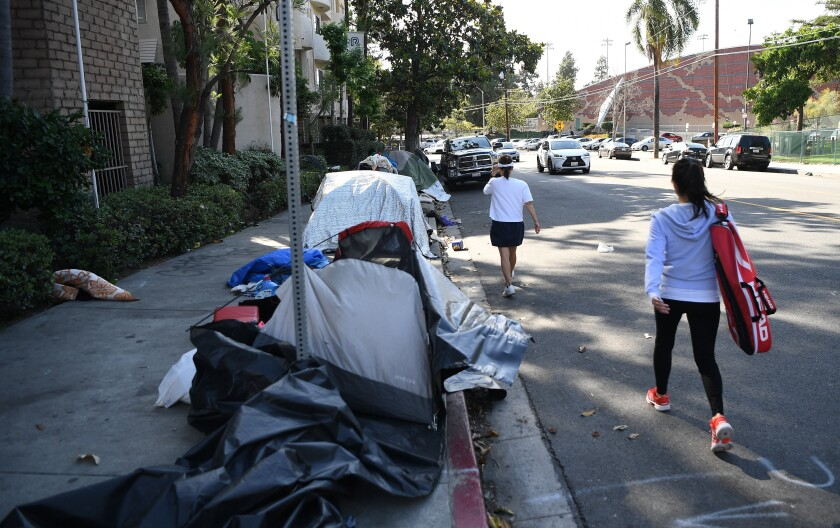 People walk past a row of tents lining a block in Los Angeles.