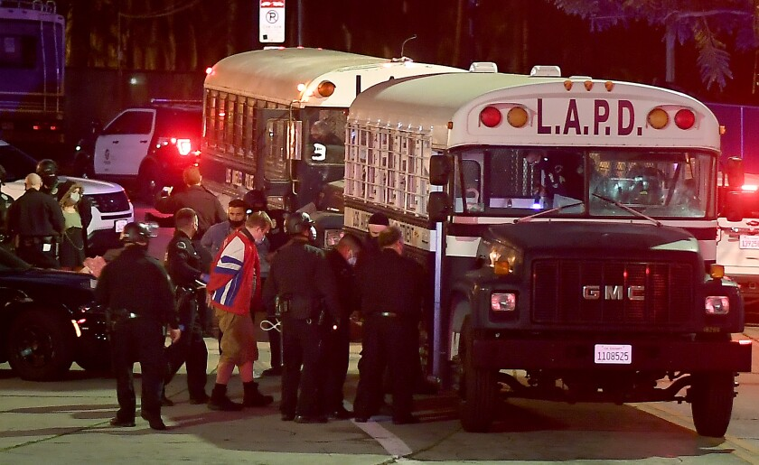 Protesters board an LAPD bus after being arrested in Echo Park