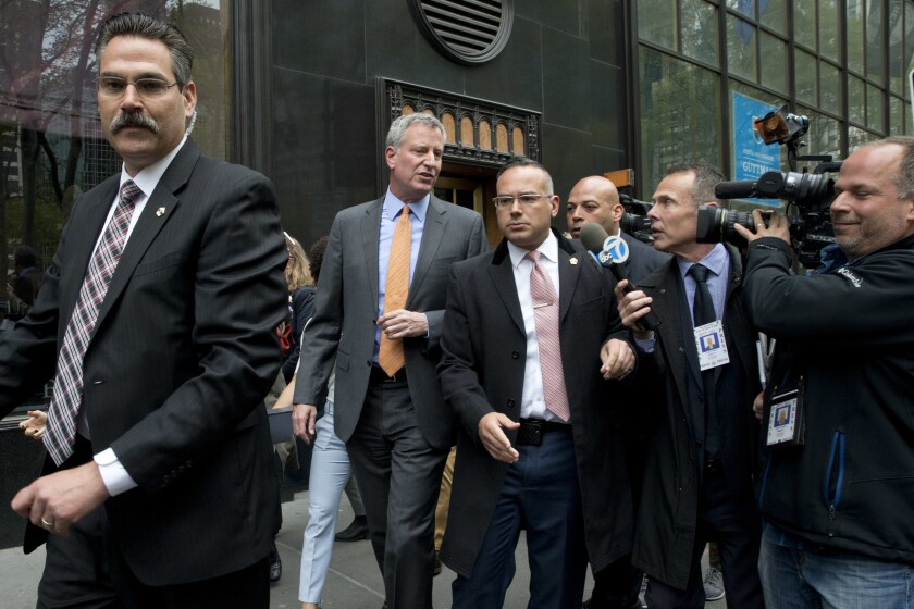 New York City Mayor Bill de Blasio is surrounded by security.