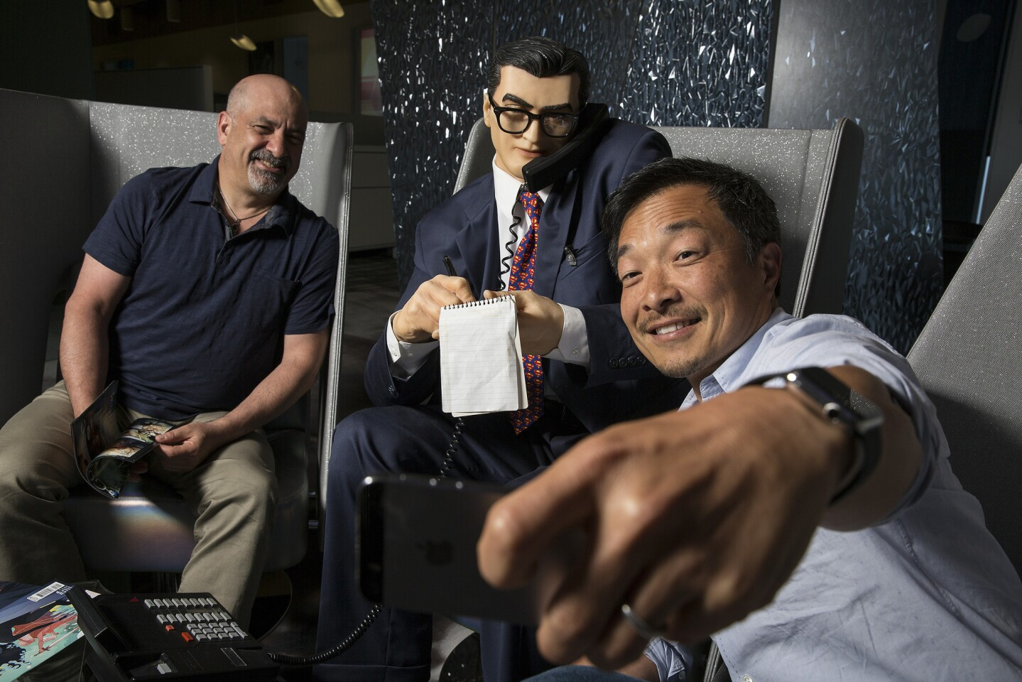 DC Entertainment publishers Dan Didio, left, and Jim Lee take more selfies with Clark Kent at the company headquarters in Burbank.