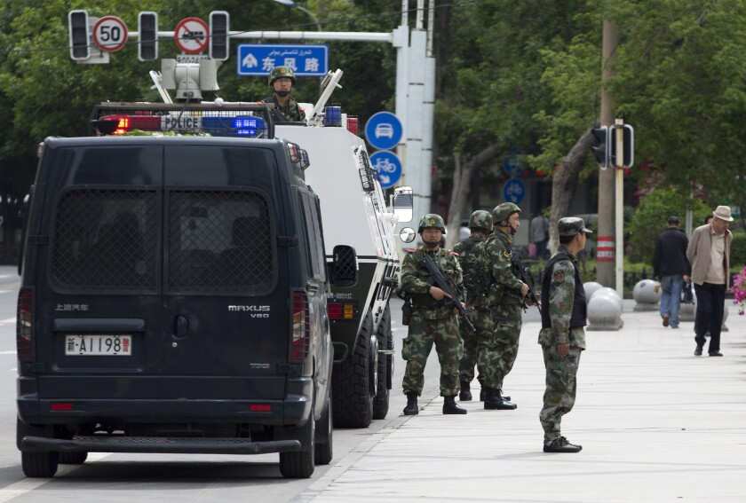 Chinese police stand guard next to their armored personnel carrier parked near the People's Square in Urumqi.