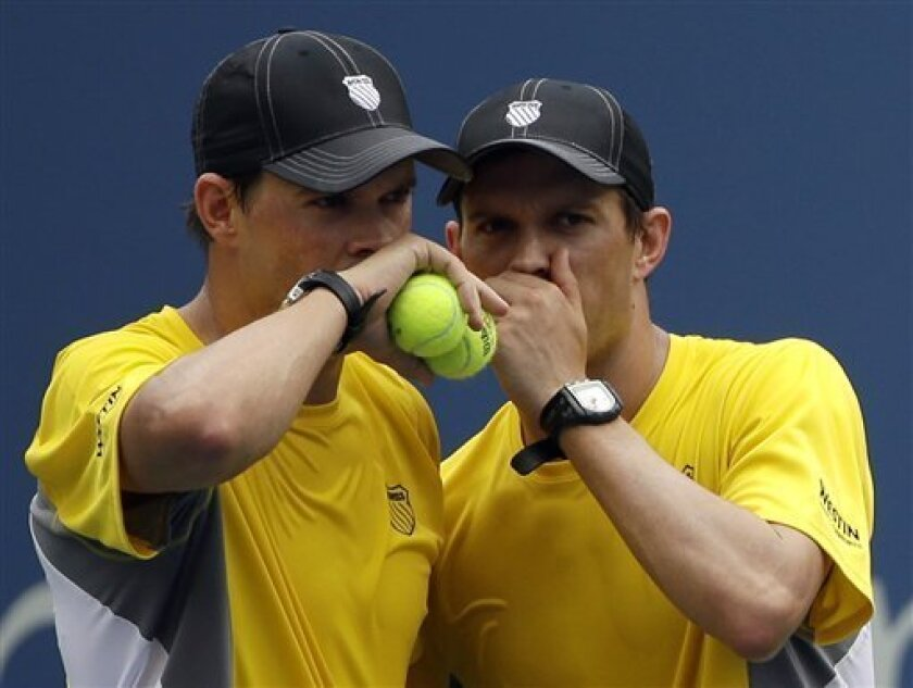 Bob Byran, left, and Mike Bryan talk between points against Daniel Nestor, of Canada, and Vasek Pospisil, of Canada, during a doubles match at the 2013 U.S. Open tennis tournament, Sunday, Sept. 1, 2013, in New York. (AP Photo/David Goldman)