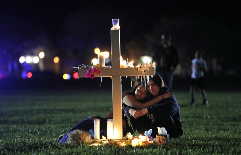 Two people embrace as they sit in front of a cross covered with candles and flowers.