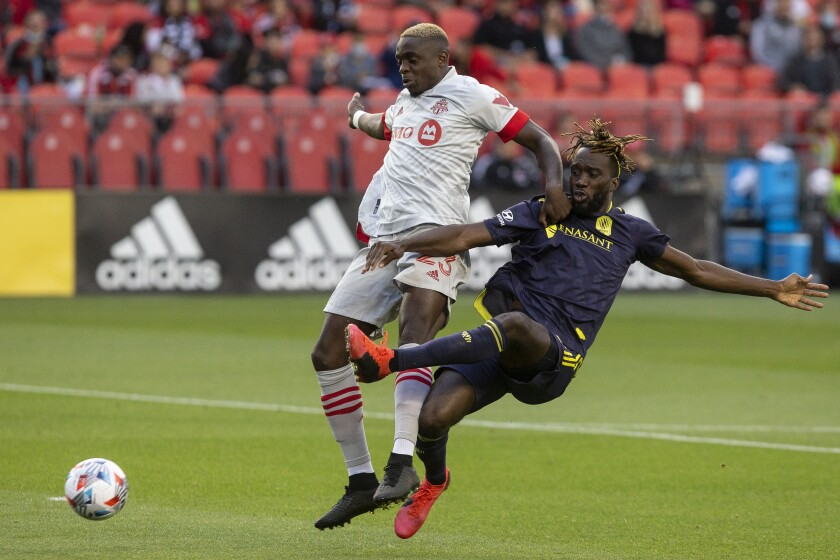 Toronto FC's Chris Mavinga, left, fends off Nashville's C.J. Sapong during the first half of an MLS soccer match, in Toronto, Sunday, Aug. 1, 2021. (Chris Young/The Canadian Press via AP)