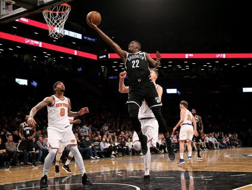 Caris LeVert (c) de New York Knicks lanza sobre Michael Beasley (i) de Brooklyn Nets, durante un partido de baloncesto de la NBA entre los Brooklyn Nets y los New York Knicks, en el Barclays Center de Brooklyn, Nueva York (EE.UU.). EFE