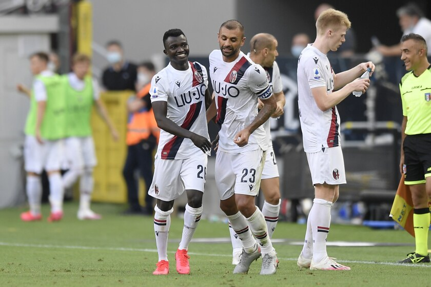 Bologna's Musa Juwara, left, celebrates with his teammate Danilo after scoring his side's 2nd goal during the Serie A soccer match between Inter Milan and Bologna, at the San Siro Stadium in Milan, Italy, Sunday, July 5, 2020. (Fabio Ferrari/LaPresse via AP)