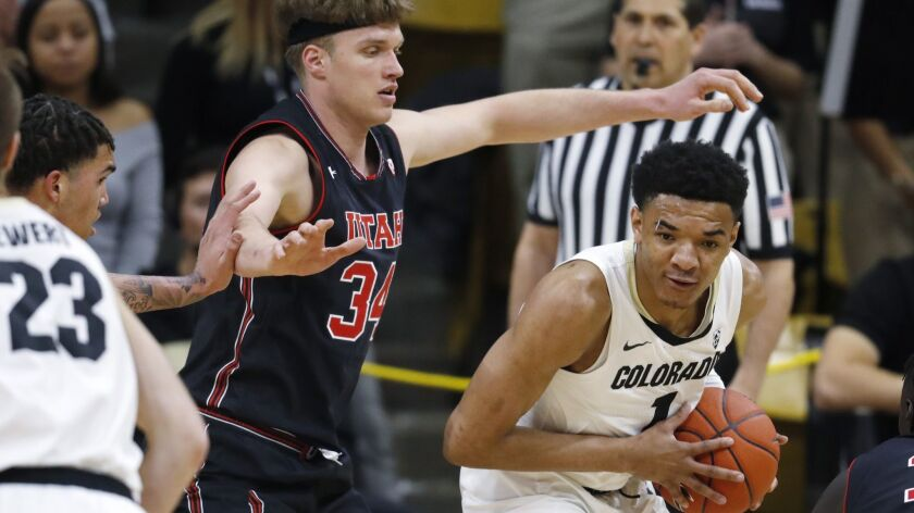Colorado guard Tyler Bey, right, collects a loose ball as Utah center Jayce Johnson defends during the first half on Saturday.