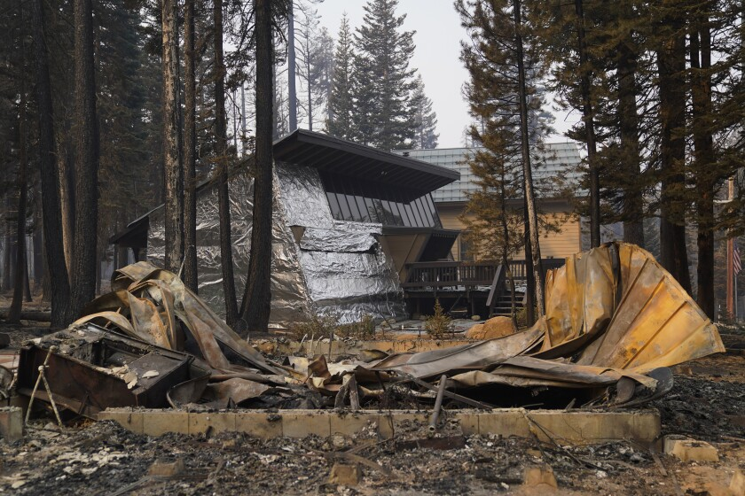 FILE - In this Sept. 2, 2021 file photo a cabin partially covered in fire-resistant material stands behind a property destroyed in the Caldor Fire in Twin Bridges, Calif. Aluminum wraps designed to protect homes from flames are getting attention as wildfires burn in California. During a fire near Lake Tahoe, some wrapped houses survived while nearby homes were destroyed. The material resembles tin foil from the kitchen drawer but is modeled after the tent-like shelters that wildland firefighters use as a last resort to protect themselves when trapped by flames. (AP Photo/Jae C. Hong,File)