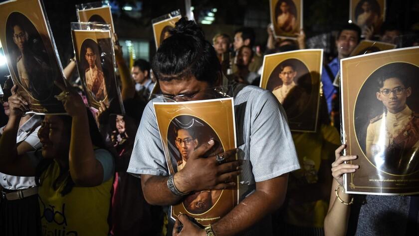 Thai people react as they hear the news of the death of Thailand's King Bhumibol Adulyadej outside Siriraj Hospital in Bangkok on Thursday.