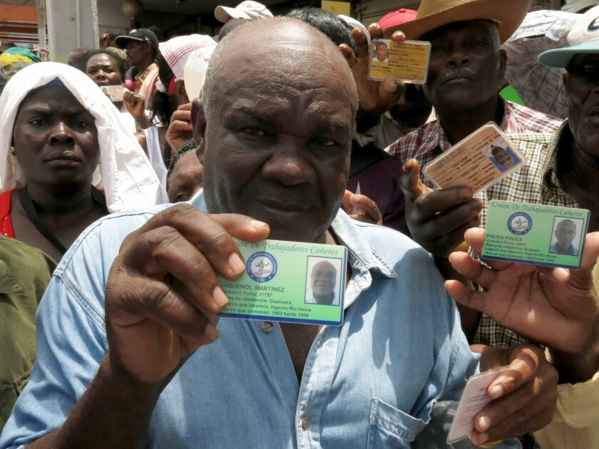 Haitian Jaquenol Martinez shows a card that proves that he has worked in the Dominican sugar cane fields since 1963, while trying to apply for a temporary resident permit, in Santo Domingo, Dominican Republic, Monday, June 15, 2015. Hundreds of Haitians are waiting in long lines throughout the Domi