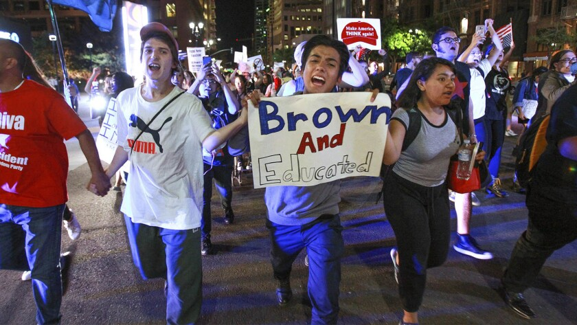 Abraham Barragan, 18, center, and around three hundred other people protest president-elect Donald Trump as they march down Broadway in downtown San Diego on Wednesday.