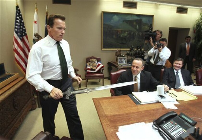 """Gov. Arnold Schwarzenegger brings the sword he used in the movie """"Conan The Barbarian,"""" to the conference table before the start of budget negotiations with legislative leaders at the Capitol in Sacramento, Calif., Tuesday, Jan. 13, 2009.  Schwarzenegger joked with State Senate President Pro Tem Da"""