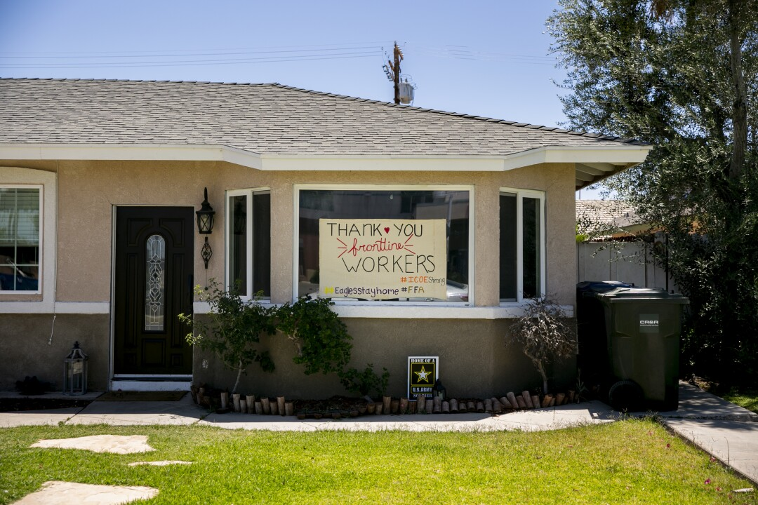 A supportive sign hangs in the window of a home across the street from the El Centro Regional Medical Center on May 20, 2020 in El Centro, California. The hospital is receiving an influx of COVID-19 patients.