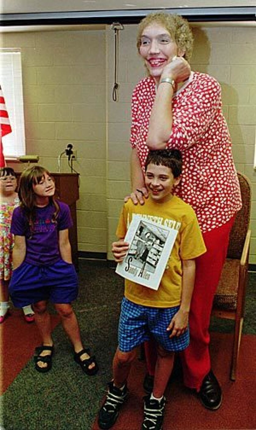 In this Sept. 2, 1995 file photo, Sandy Allen, poses for a picture with Will Denk, at the library in Shelbyville, Ind. The 7-foot-7 Allen considered the world's tallest woman died early today at a nursing home in her hometown of Shelbyville. She was 53.