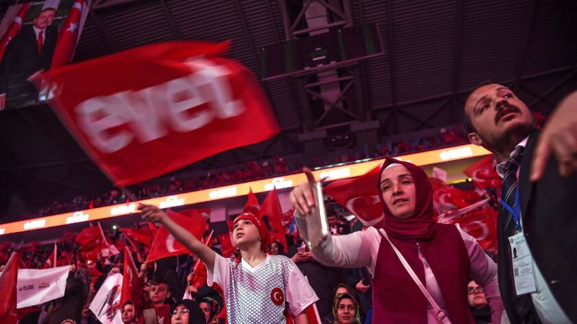 """Supporters wave Turkey's national flags and a flag reading """"Yes"""" in Turkish (L) during a campaign ra"""