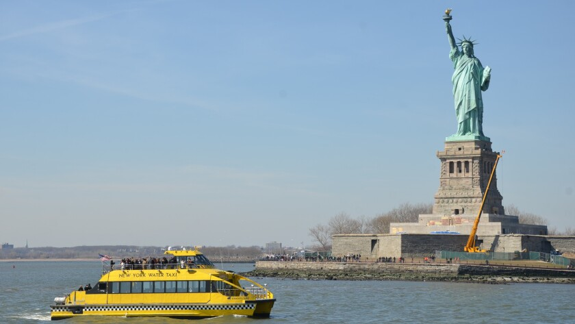 Like a Manhattanite hailing a cab, the State of Liberty towers over a New York Water Taxi.