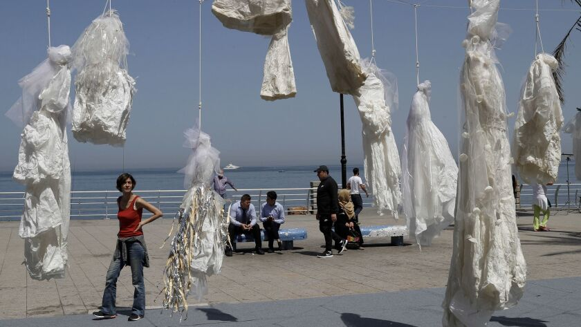 A woman looks towards white wedding dresses displayed as a desecrated symbol by the Lebanese NGO Aba