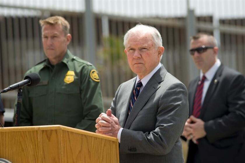 El fiscal general de los Estados Unidos, Jeff Sessions (c), escucha la pregunta de un reportero durante una conferencia de prensa celebrada en la valla fronteriza entre los Estados Unidos y México. EFE/Archivo