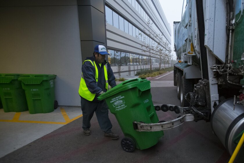Daniel Reyes prepare one of the containers of recycled food container for the loader where it will be emptied into the large truck and later will be transported to the landfill.