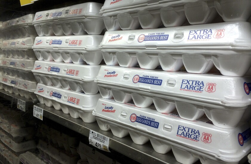 Eggs packed in polystyrene containers sit on a supermarket shelf.