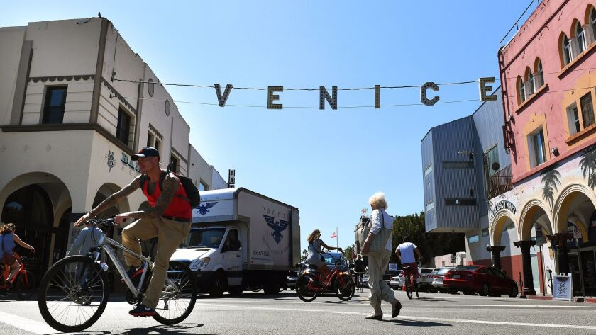 VENICE-CA-SEPTEMBER 14, 2016: Pedestrians and bicyclists cross a street in Venice. (Christina House