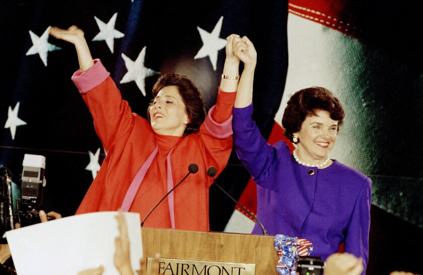 Barbara Boxer, left, and Dianne Feinstein raise their arms in victory and wave to supporters at a 1992 election rally in San Francisco.