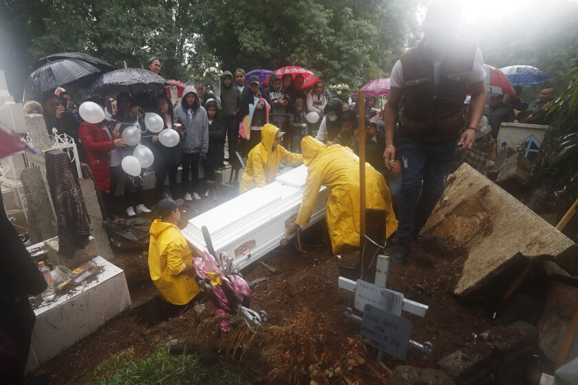 A coffin containing the remains of one of three children shot dead in a video-game arcade, is lowered into a freshly dug grave in Uruapan, Mexico, Wednesday, Feb. 5, 2020. Relatives gathered in a driving rain Wednesday to mourn and bury three children, a 17-year-old and five adults shot to death in the Monday attack, in the Mexican western state of Michoacan. (AP Photo/Marco Ugarte)