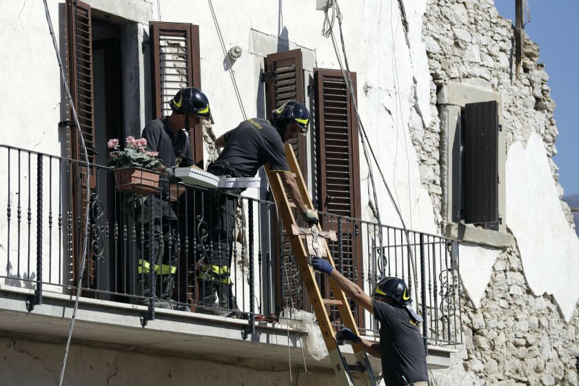 Firefighters recover a crucifix and personal belongings from a damaged house in the village of Rio, central Italy, Sunday, Aug. 28, 2016. Bulldozers with huge claws pulled down dangerously overhanging ledges Sunday in Italy's quake-devastated town of Amatrice as investigators worked to figure out i