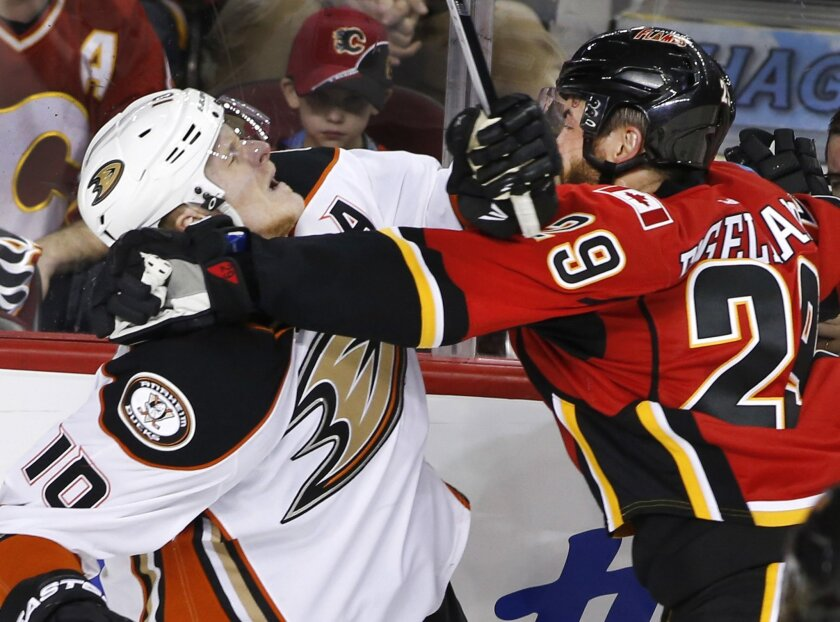 Anaheim Ducks' Corey Perry, left, is hit by Calgary Flames' Deryk Engelland during second period NHL action in Calgary, Alberta, Monday, Feb. 15, 2016. (Larry MacDougal/The Canadian Press via AP) MANDATORY CREDIT