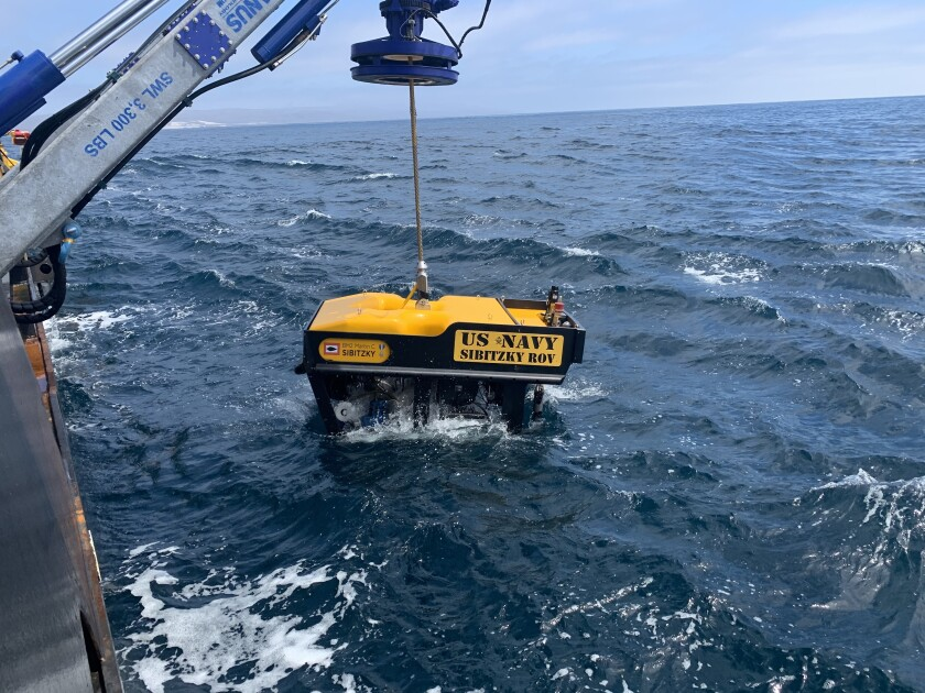 Undersea Rescue Command deploys a remotely operated vehicle from the deck of the HOS Dominator.