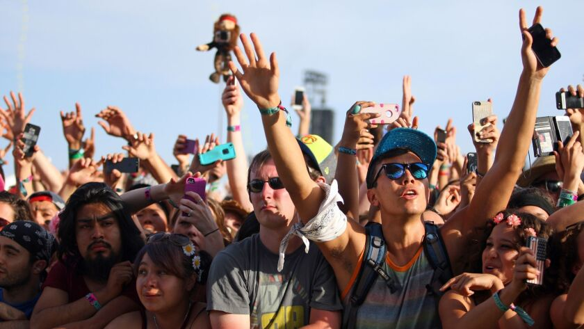 FILE - In this April 19, 2014 file photo, festival goers hold up cameras and phones during the 2014