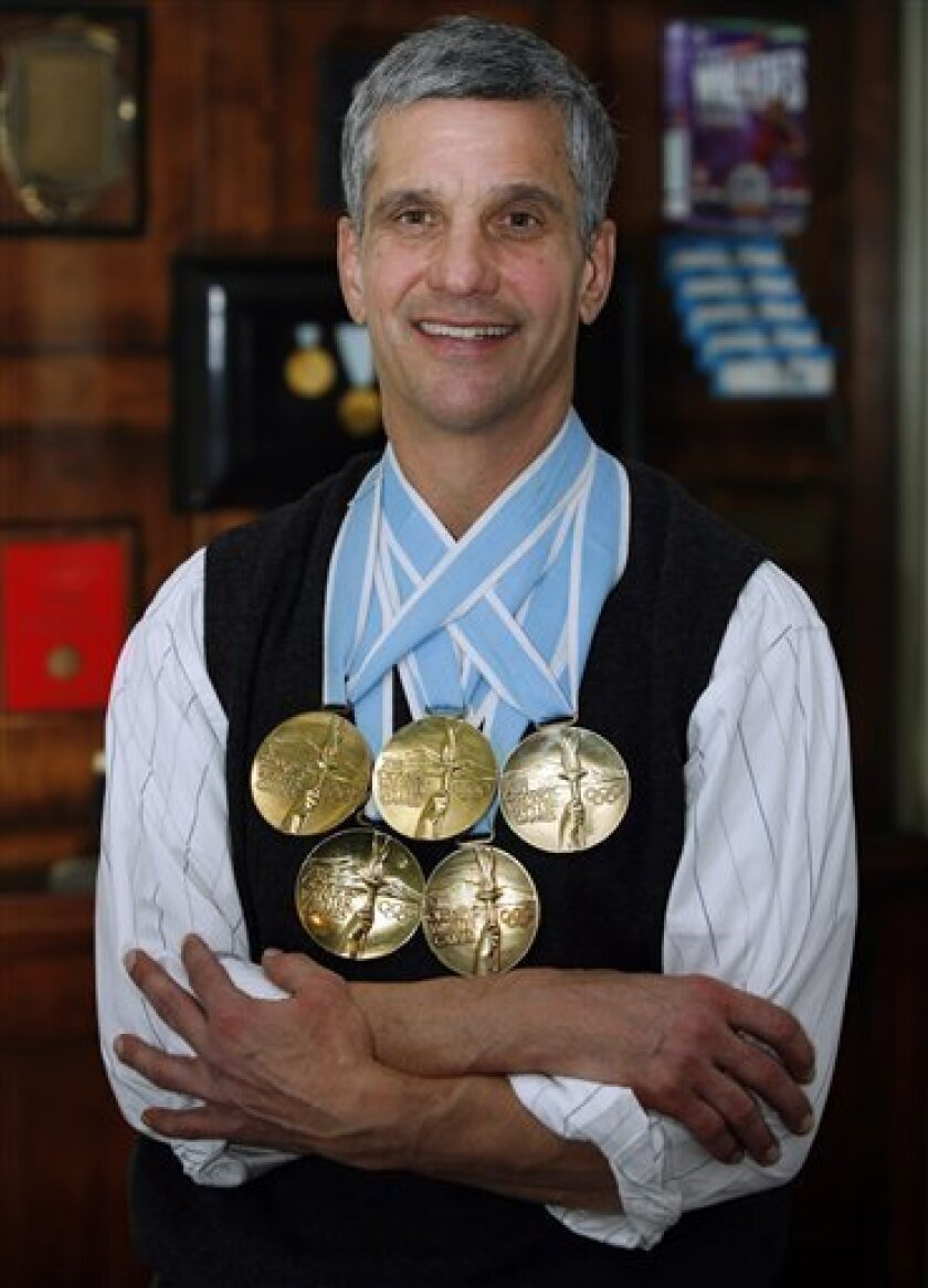 Dr. Eric Heiden, winner of 5 gold medals in speed skating at the 1980 Olympic Games in Lake Placid, is shown with his medals infront of a display case of memorabilia at his medical practice Friday, Jan. 29, 2010, in Park City, Utah. Heiden also raced bicycles in the 1986 Tour de France before going on to medical school and becoming an Orthopedic Surgeon. (AP Photo/Steve C. Wilson)