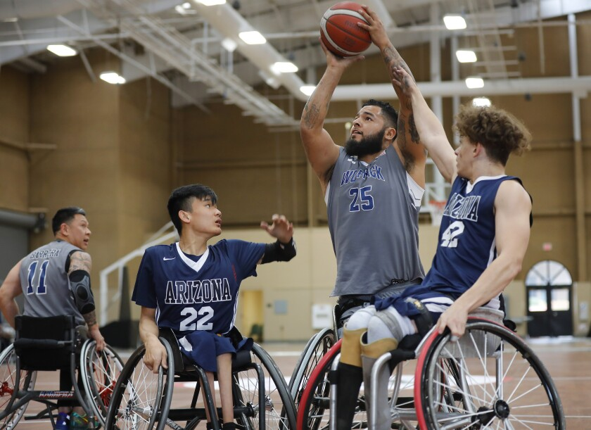 Jorge Salazar, center, of the Naval Medical Center San Diego Wolfpack shoots as Michael Seo, left, and Jackson Stone of the University of Arizona defend during the 4th Annual Brad Rich Invitational wheelchair basketball tournament at the Del Mar Fairgrounds on Feb. 9, 2020.