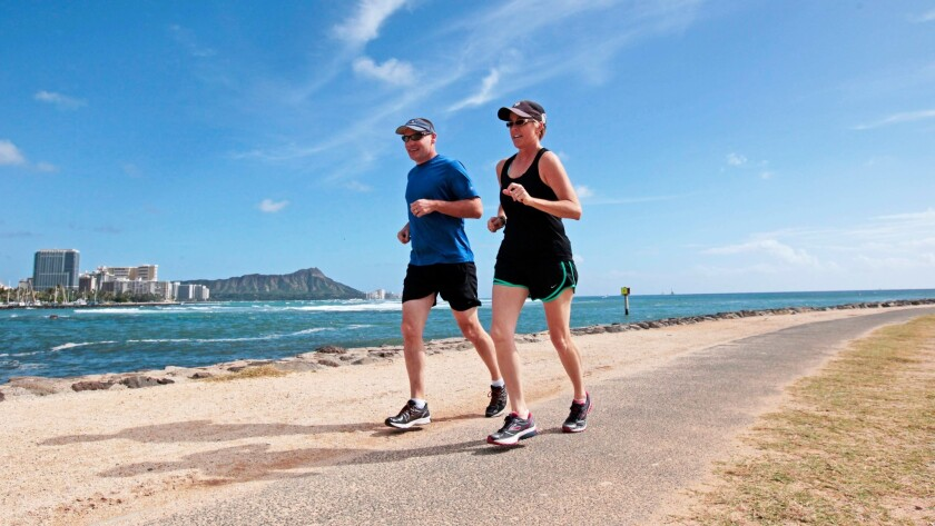 Honolulu residents Jon and Jen Grems take a run through Ala Moana Beach Park. A new run takes participants on a 60-minute workout past some of the Waikiki hotels to Diamond Head and beyond.