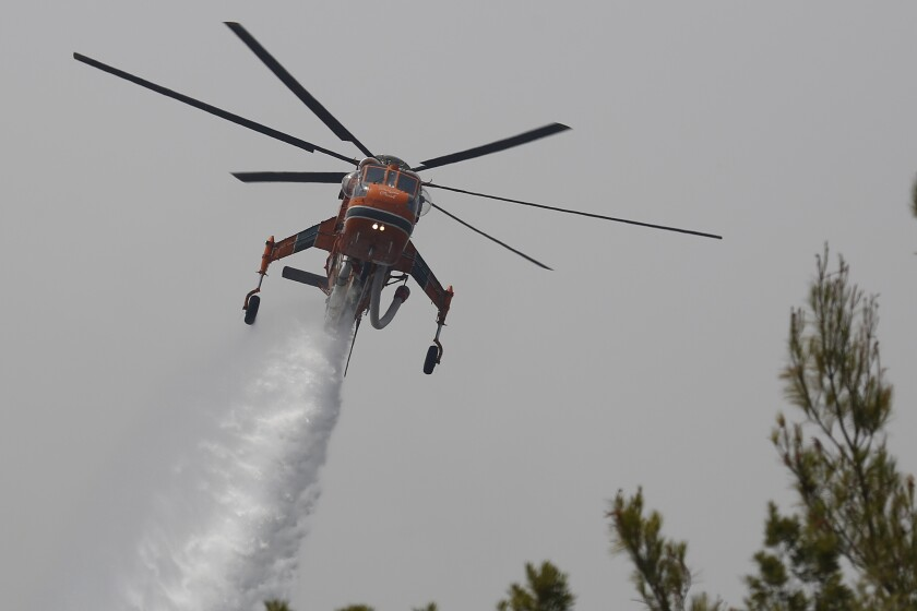 An helicopter drops water over a fire in Galatsonas village on Evia island, about 184 kilometers (115 miles) north of Athens, Greece, Wednesday, Aug. 11, 2021. Hundreds of firefighters from across Europe and the Middle East worked alongside Greek colleagues in rugged terrain Wednesday to contain flareups of the huge wildfires that ravaged Greece's forests for a week, destroying homes and forcing evacuations. (AP Photo/Lefteris Pitarakis)