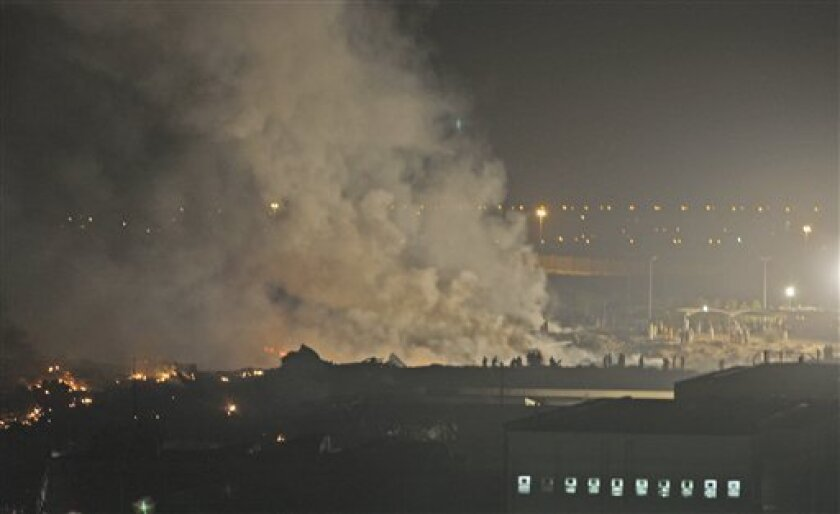 Smoke rises from the site of a cargo plane crash in Dubai, United Arab Emirates, Friday Sept. 3, 2010. Officials say a UPS cargo plane with two crew members on board has crashed shortly after takeoff outside Dubai. There was no immediate word on casualties. (AP Photo/Kamran Jebreili)