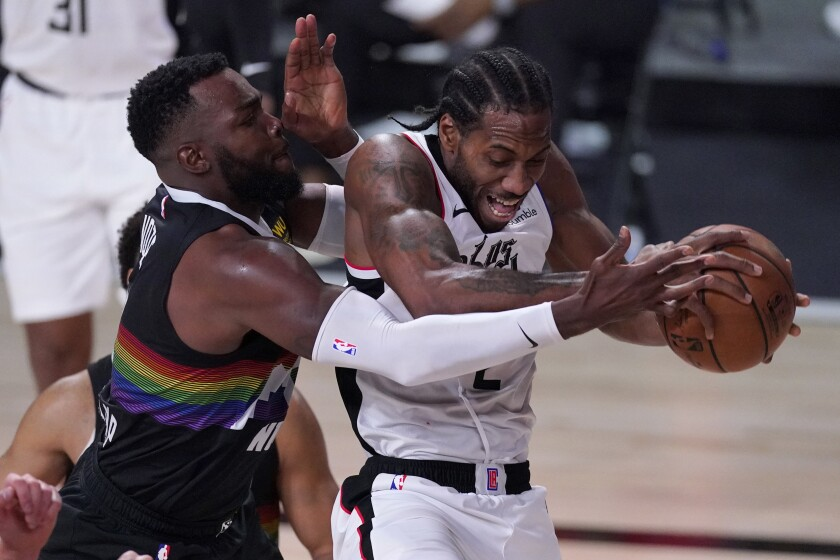 The Clippers' Kawhi Leonard comes down with the ball against the Denver Nuggets' Paul Millsap.