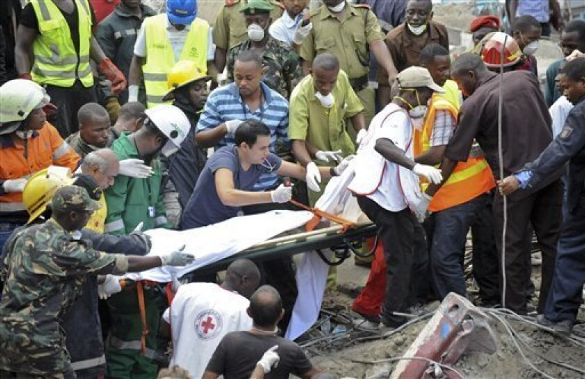 Rescuers from the Tanzania Red Cross carry away a body from the rubble of a collapsed building in downtown Dar es Salaam, Tanzania Friday, March 29, 2013. A Tanzanian police official says the multi-storey building was in the final stages of its construction and most of the people caught up in the c