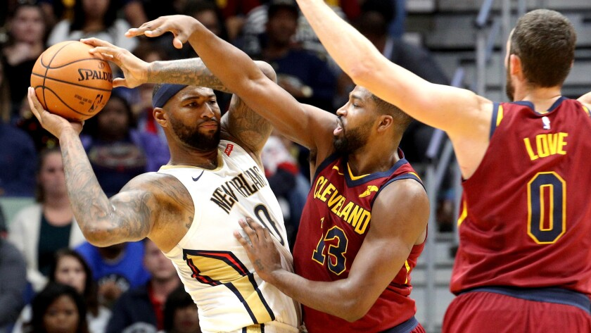 Pelicans center DeMarcus Cousins looks to pass against the double-team defense of Cleveland big men Tristan Thompson (13) and Kevin Love on Saturday.