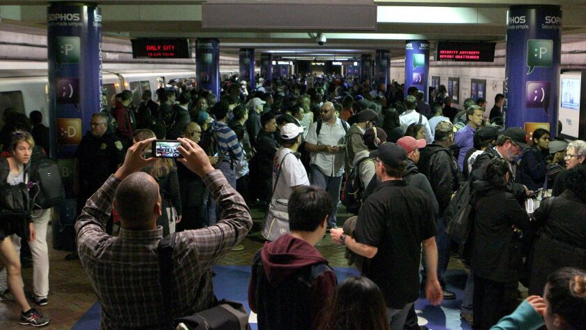 Commuters wait at the Bay Area Rapid Transit (BART) Montgomery street station in San Francisco during a service delay.