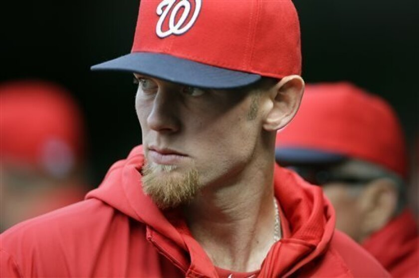 Washington Nationals starting pitcher Stephen Strasburg stands in the dugout during an exhibition baseball game against the New York Yankees at Nationals Park on Friday, March 29, 2013, in Washington. The Yankees won 4-2. Strasburg is expected to start opening on Monday. (AP Photo/Alex Brandon)