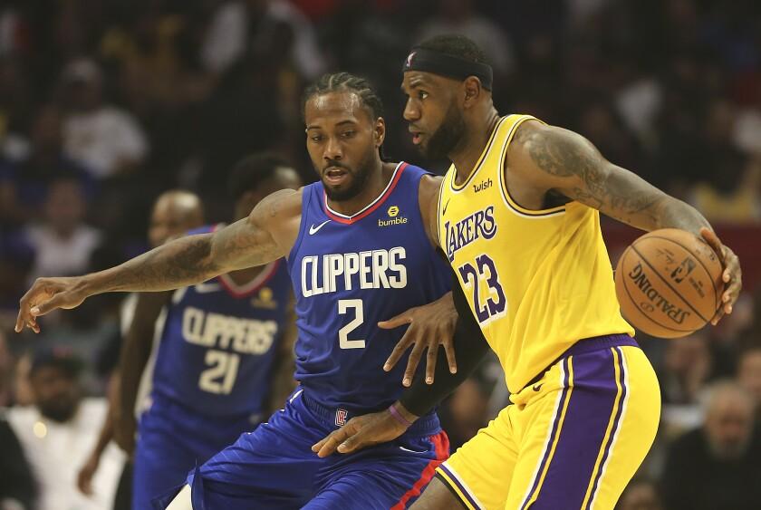 Clippers forward Kawhi Leonard guards Lakers forward LeBron James.