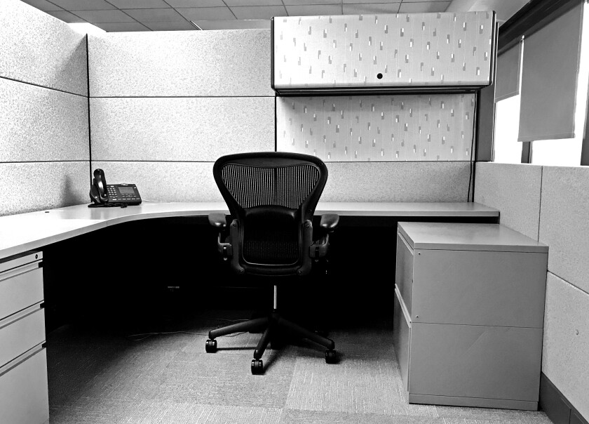 An empty office cubicle with a chair and a desk.