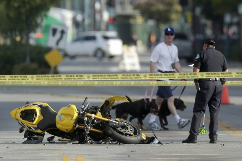 A man walks by with his dogs as an LAPD officer investigates a crash scene in North Hollywood on Saturday morning.