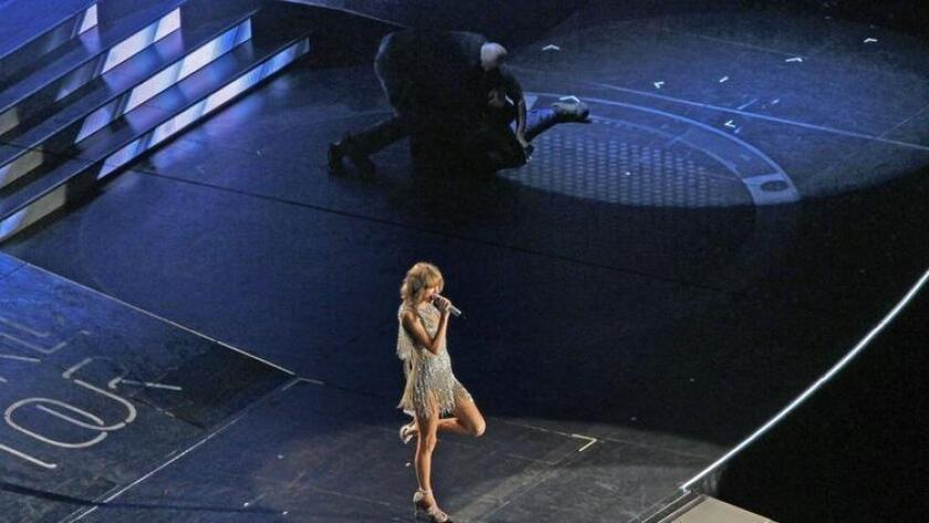 Security guards take away a fan who jumped on stage during the Taylor Swift concert at Petco Park. (/ K.C. Alfred)