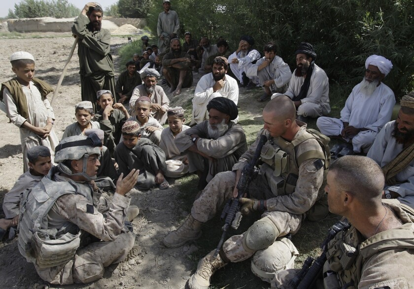 US Marine Sgt. Isaac Tate, left, and Cpl. Aleksander Aleksandrov, center, interview an Afghan man with a translator