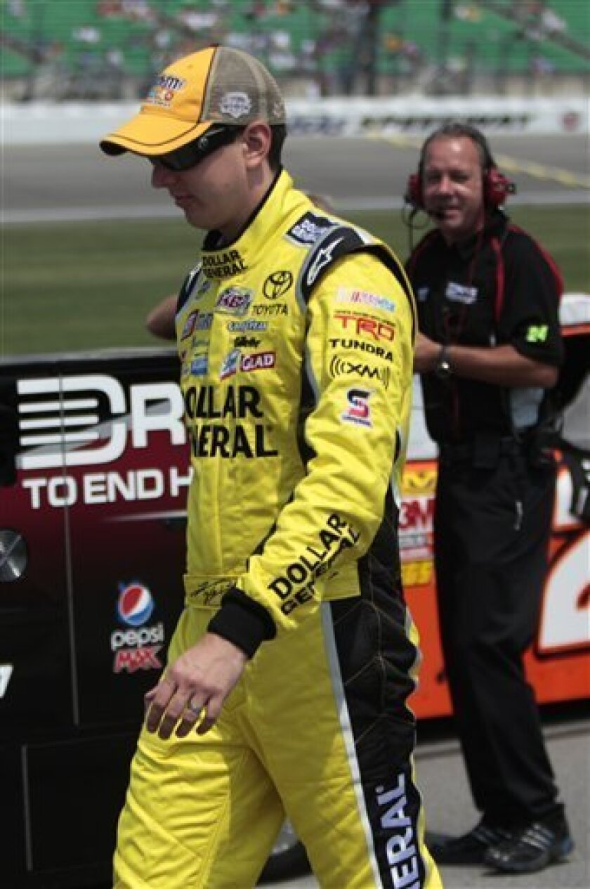 Sprint Cup Series driver Kyle Busch walks toward his car during qualifying for Sunday's NASCAR Sprint Cup Series auto race at Kansas Speedway Saturday, June 4, 2011, in Kansas City, Kan. (AP Photo/Orlin Wagner)